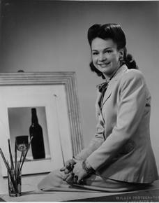Fran Taylor, the owner of Gay Fad Studios, sitting in front of a picture and some paint brushes.